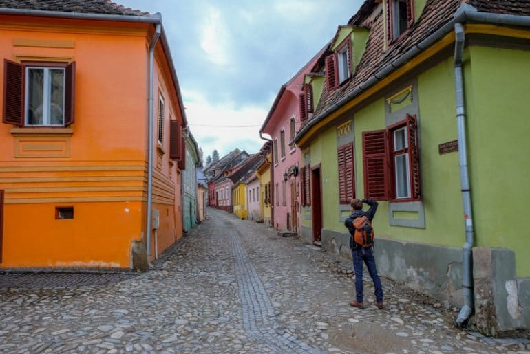 colourful houses and cobblestone street with boy taking photo