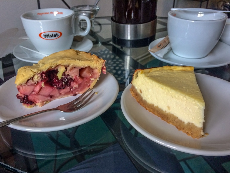 cheesecake and pie with coffee mugs on table
