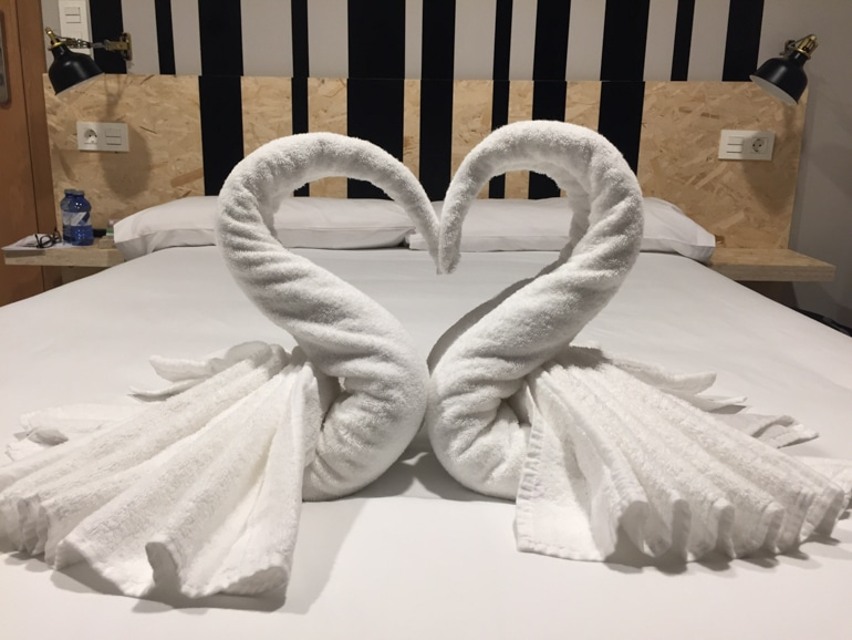 white towel swans on white bed