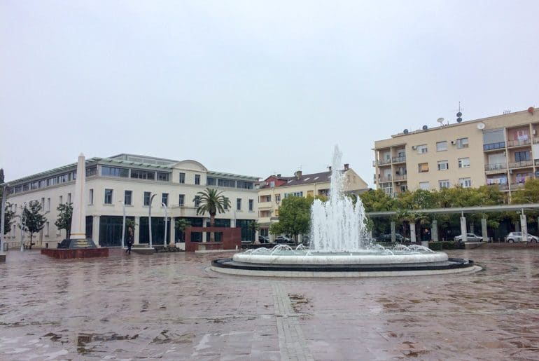 fountain with red tiles and buildings around podgorica