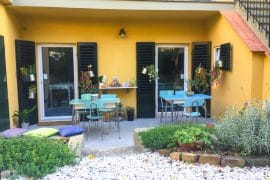 blue tables on yellow patio in florence hostel penguin and pia
