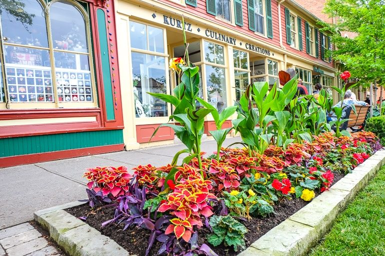 colourful gardens with sidewalk and stores behind in niagara on the lake
