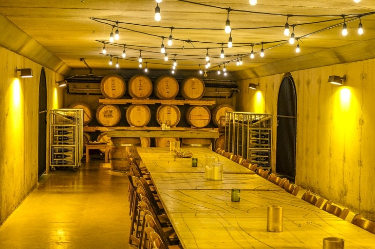 wooden barrels in cellar with wooden table and lights inniskillin wine tour
