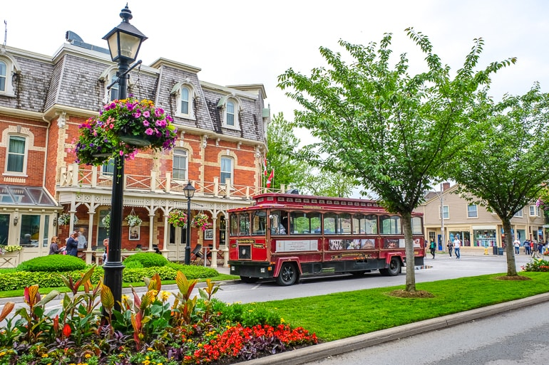 Roter Trolley geparkt hinter altem Hotel und grünen Gärten in Niagara on the Lake Ontario Kanada