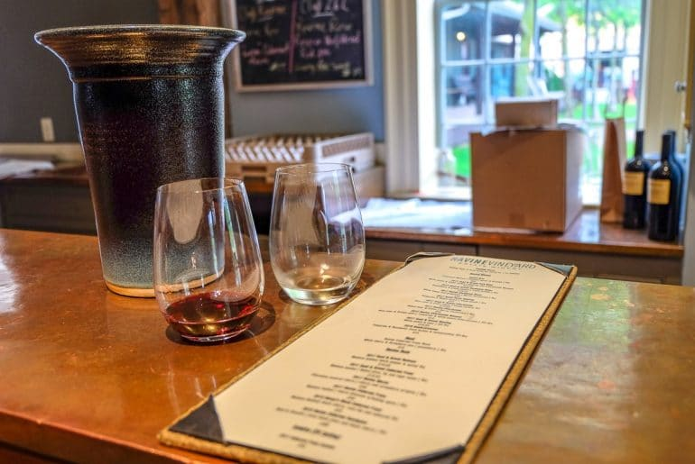 Weingläser auf Tresen aus Holz mit Weinflaschen im Hintergrund Niagara on the Lake Weintour