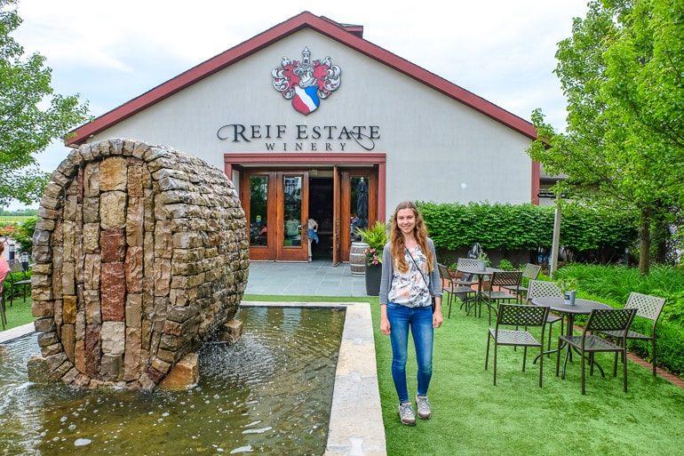 Frau neben Springbrunnen vor Eingang zu Weingut Reif Estates