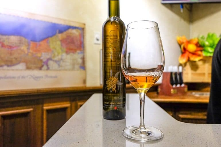 ice wine in glass on counter with wine bottle behind niagara on the lake wine tours