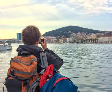 guy with backpacks on taking photo of harbour in croatia