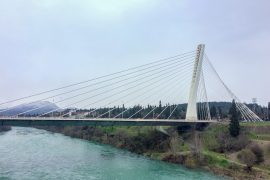 white steel bridge over blue river podgorica