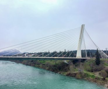 white steel bridge over blue river podgorica