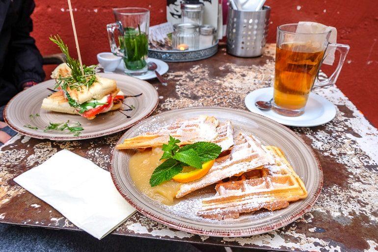Waffel mit Apfelmus und Panini auf Teller auf Tisch in Cafe