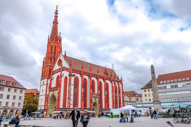 red and white church with tower in open town square wurzurg germany