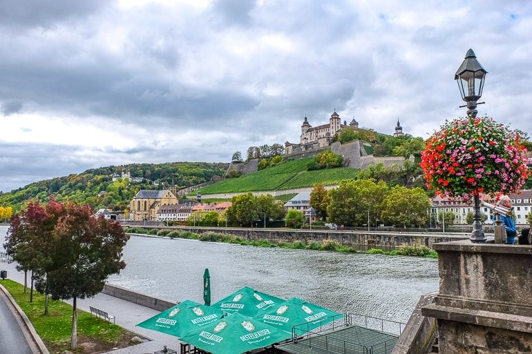 castle on hill with river below and green umbrellas in wurzburg germany