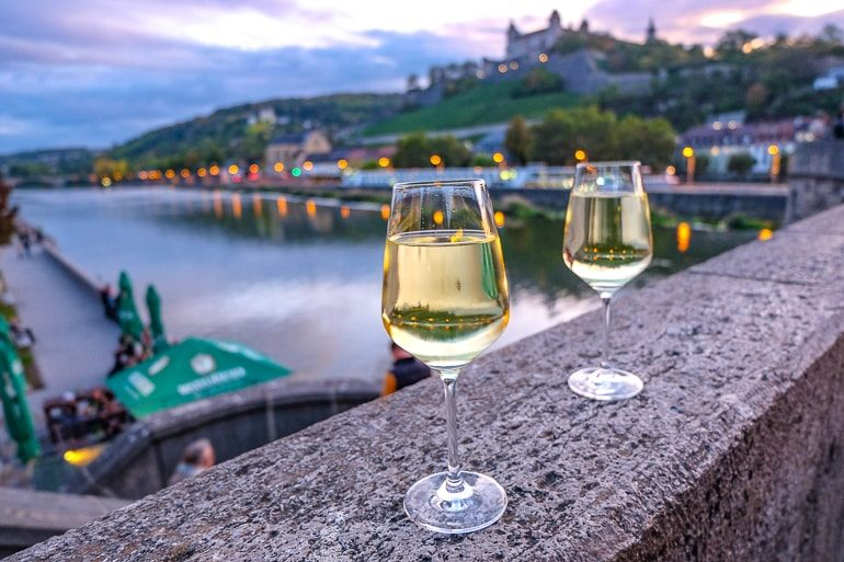 two wine glasses on ledge of old stone bridge with river and castle behind things to do in wurzburg