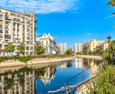 old apartment buildings with blue river flowing in front where to stay in bucharest