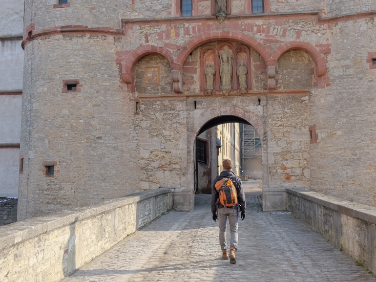 boy with orange backpack walking into marienberg fortress wurzburg