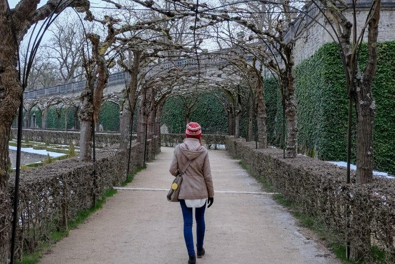 girl with red hat walking through symmetrical garden in wurzburg germany