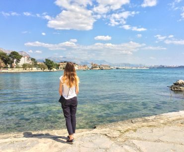 blonde girl standing on shoreline in croatia with blue water couple travel quotes