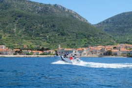 boat making waves with croatian island in background