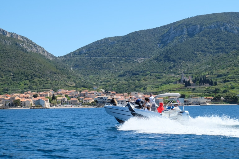 speed boat on blue ocean with old town and green mountain behind croatia island hopping