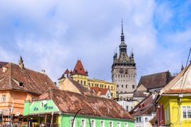 colourful houses and tower in romania with blue sky day trips from brasov