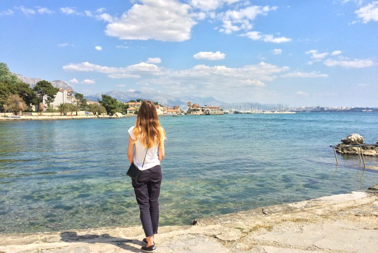 blonde girl looks out over blue water and old town on day trips from split
