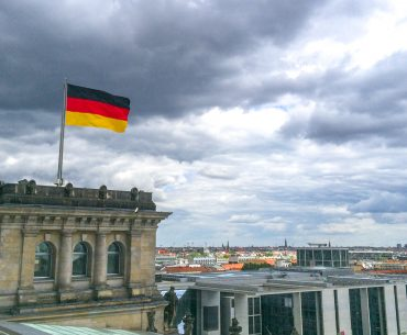 german flag flying with city behind traveling to germany for the first time