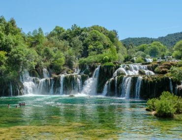 waterfall in croatia with green trees and blue sky krka national park
