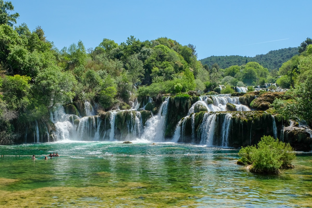 waterfall in croatia with green trees and blue sky krka