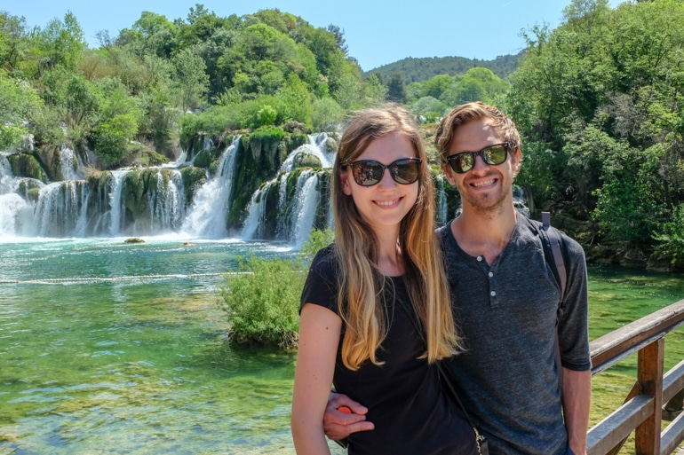 boy and girl with sunglasses pose in front of waterfall krka national park