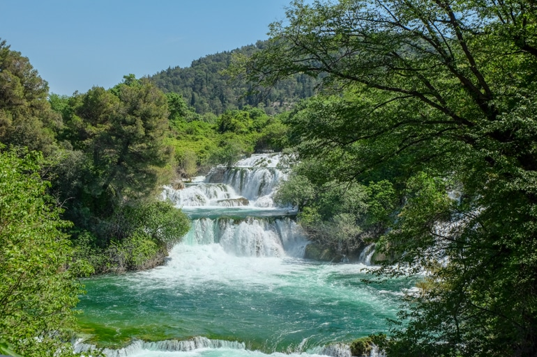 blue waterfalls with green trees in Krka National park