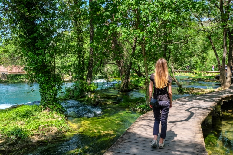 girl walking through trees on wooden path with river underneath krka national park