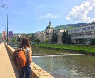 girl with orange backpack standing by river in sarajevo