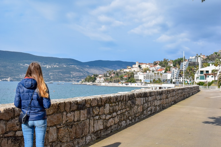 girl in blue jacket standing on seaside promenade in herceg novi