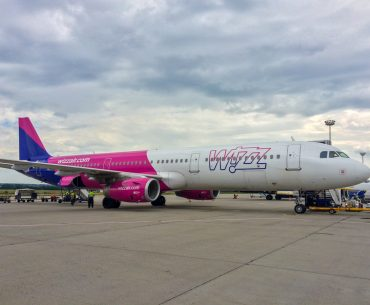 pink and white wizz air airplane on runway