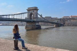 girl sitting on river edge with bridge behind her on eastern europe itinerary
