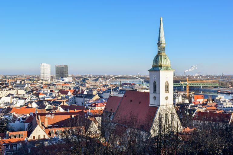white church tower amongst blue sky in bratislava slovakia