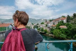 boy with burgundy backpack looks at blue river and stari most bridge mostar to dubrovnik