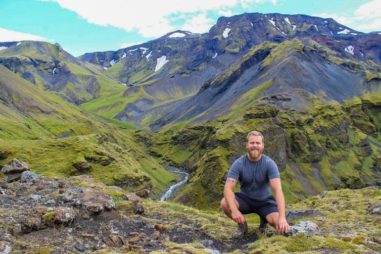icelandic local kneeling with green rocky mountains in background planning a trip to iceland