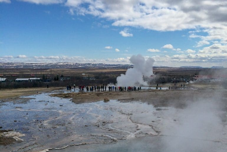 people stand around geyser in iceland planning a trip to iceland