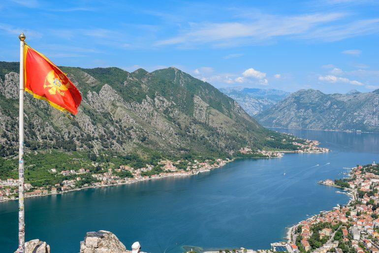 Flagge von Montenegro mit Bucht von Kotor im Hintergrund