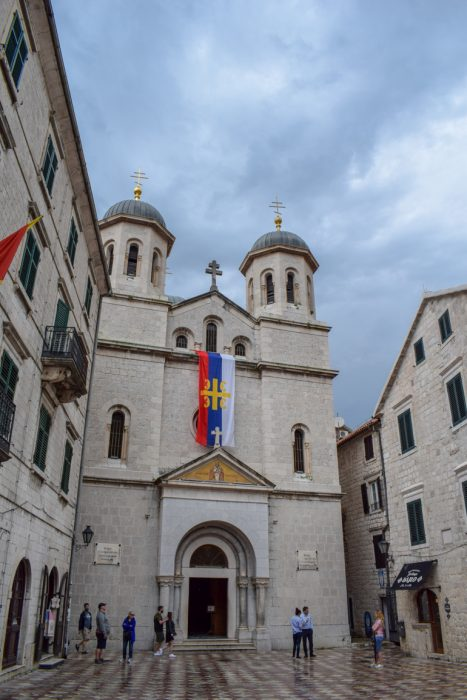 stone church with flag and dome towers in old town kotor things to do in kotor