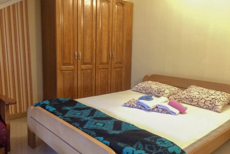 bed with towels on it and wardrobe in hostel room