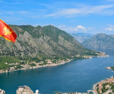 montenegro flag flying with blue bay of kotor in background penguin and pia