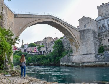 blonde hair girl standing under old bridge in mostar with river below things to do in mostar
