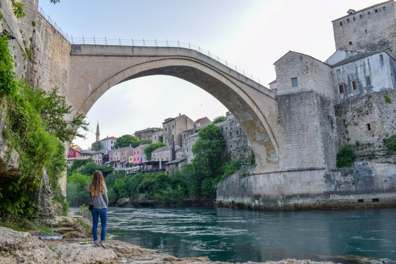 girl standing under bridge with blue river in mostar things to do in dubrovnik croatia