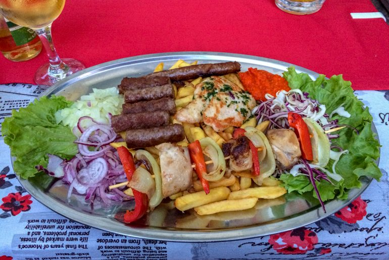 grilled meat platter with fried and vegetables in red table cloth in mostar bosnia