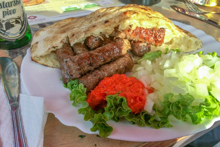 sausages with red sauce in pita bread on white plate in mostar
