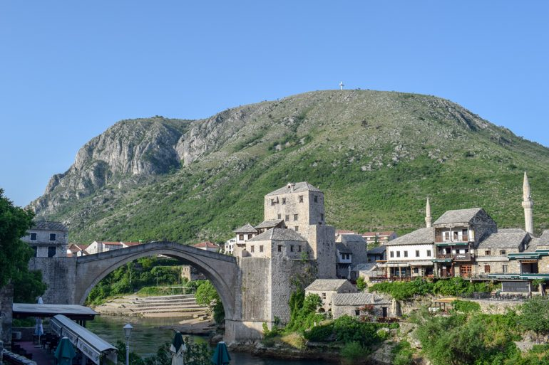 old town bridge in mostar with sun rising and mountain in background