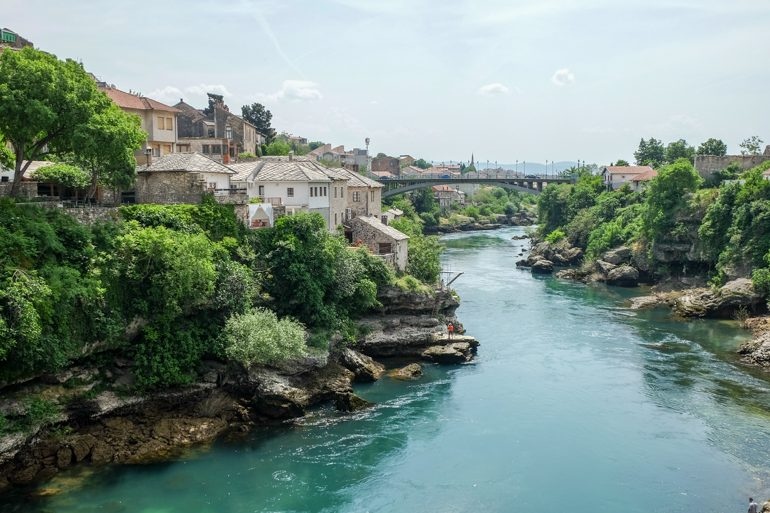 blue neretva river in mostar bosnia with old houses and blue sky